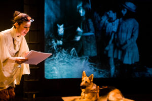 Star of happiness promotional shot: Godin with lamp on head and braille paper and Igor GuideDog, and three little girls in projected background.