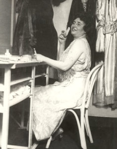 Helen Keller in her dressing room, 1920. Helen is seated before a table, facing left. Behind her is a row of many robes and gowns. On the table appears to be makeup, and her left hand, resting on the edge of the table holds a brush. Her right hand is holding a powder puff to her right cheek. Her head is tossed back slightly and she is smiling broadly as though enjoying playing to the camera.