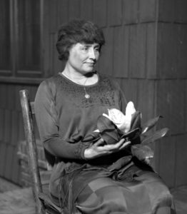 Helen Keller, with full dark hair and wearing a long dark dress, her face in partial profile, sits in a simple wooden chair. A locket hangs from a slender chain around her neck; in her hands is a magnolia, its large white flower surrounded by dark leaves.