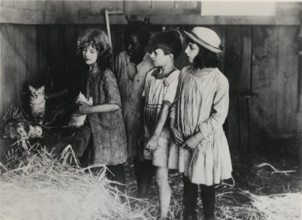 Publicity still from the 1919 film Deliverance about Keller's childhood. The fictional Helen is at far left of the group and her three playmates are gathered behind her. They look on as Helen holds a kitten; several other kittens can be seen amid a pile of straw at left.