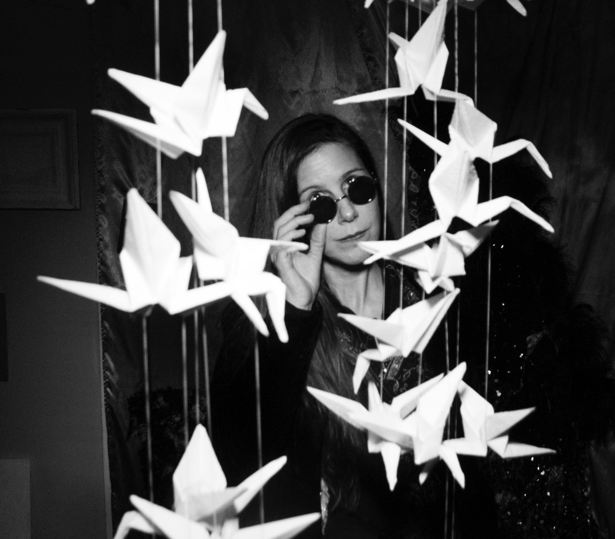 Godin tilting sunglasses at hanging braille origami cranes.