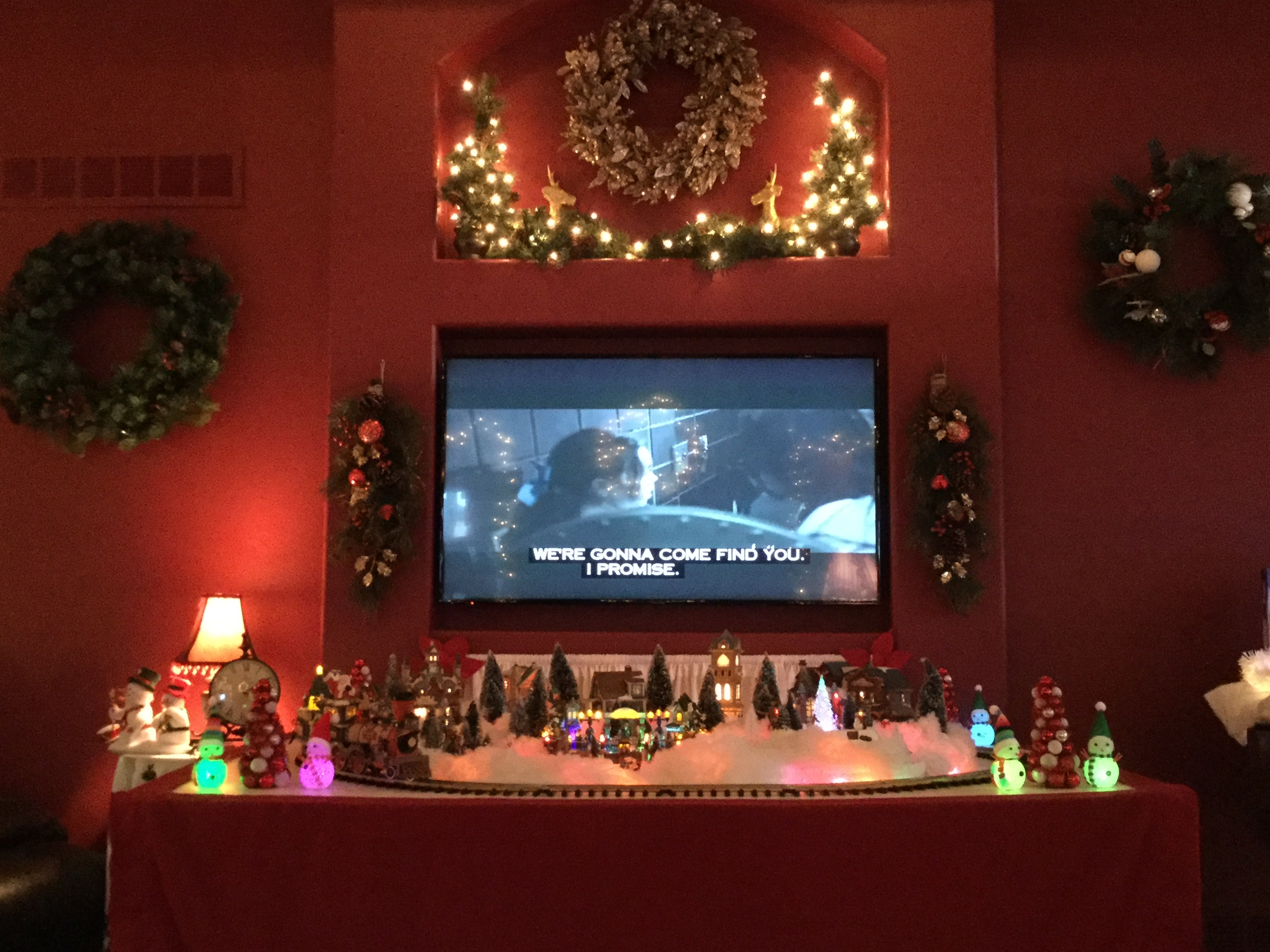 "Winter village with train set in front of TV playing scary movie with closed caption, ""We're gonna come find you. I promise."""