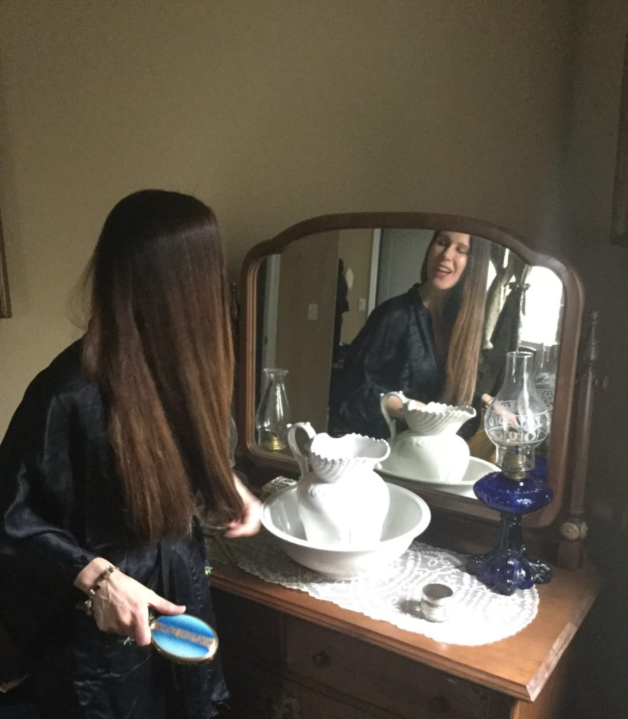 Godin brushing hair reflected in antique vanity mirror