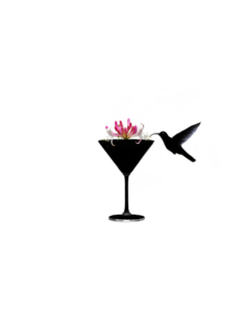 A humming bird drinks from a martini glass of honeysuckle.