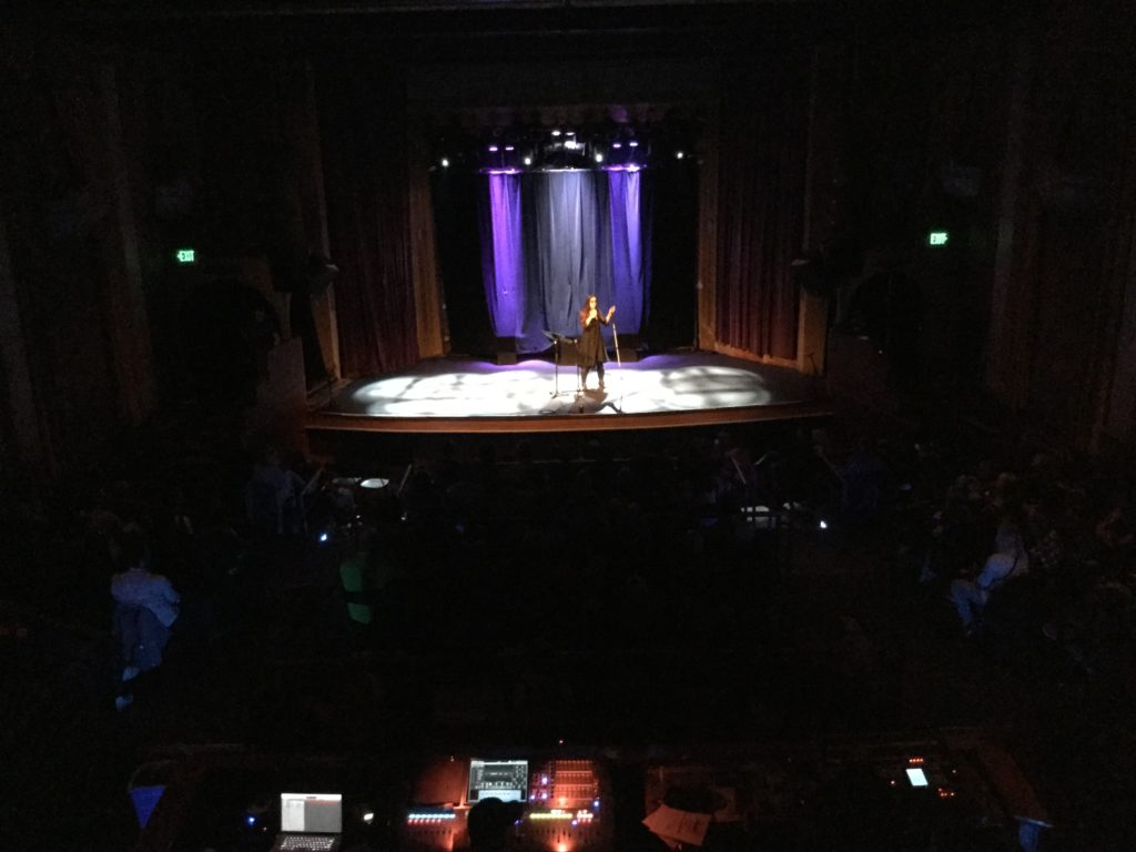 Photo of Leona Godin on the large Bluebird Theater stage taken from the balcony. She stands alone with a mic and her cane, Moses, wearing black and sunglasses.